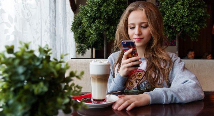 Mädchen mit Smartphone am Tisch