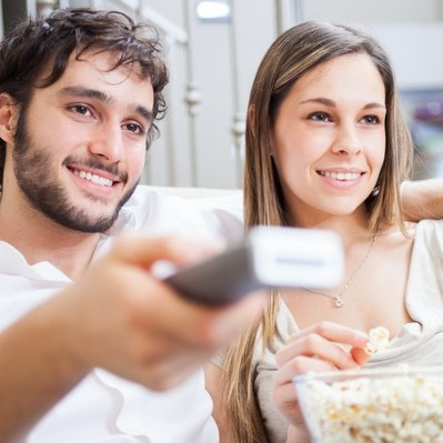 Mann und Frau mit Popcorn und Fernbedienung